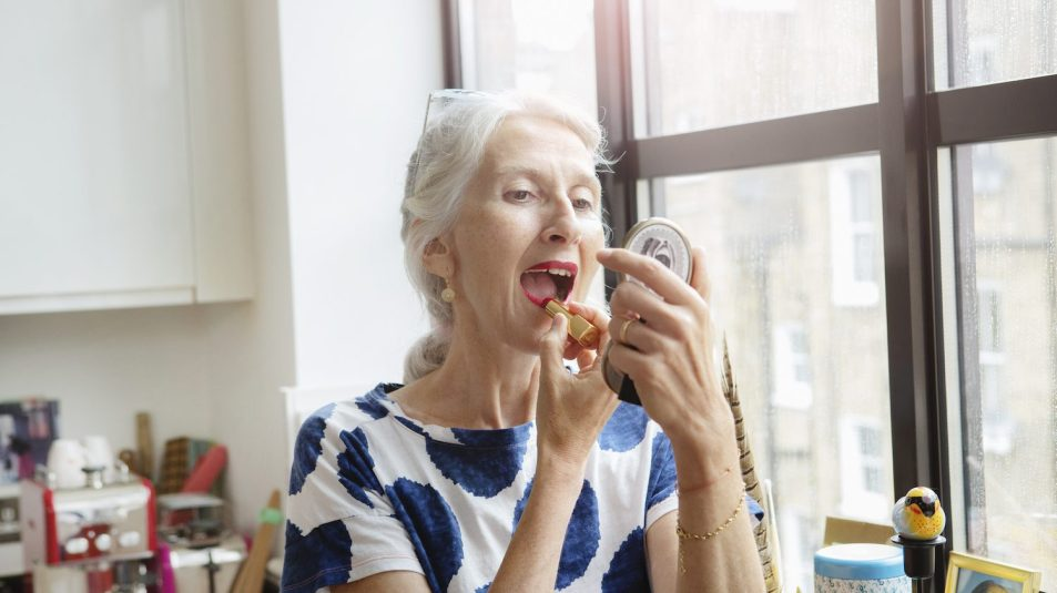 Mature woman putting on lipstick at home