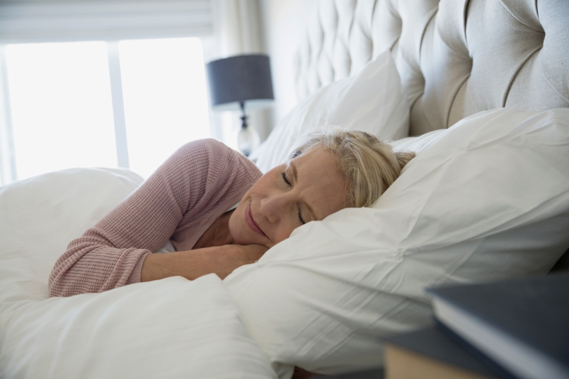 older woman sound asleep in an all-white bed