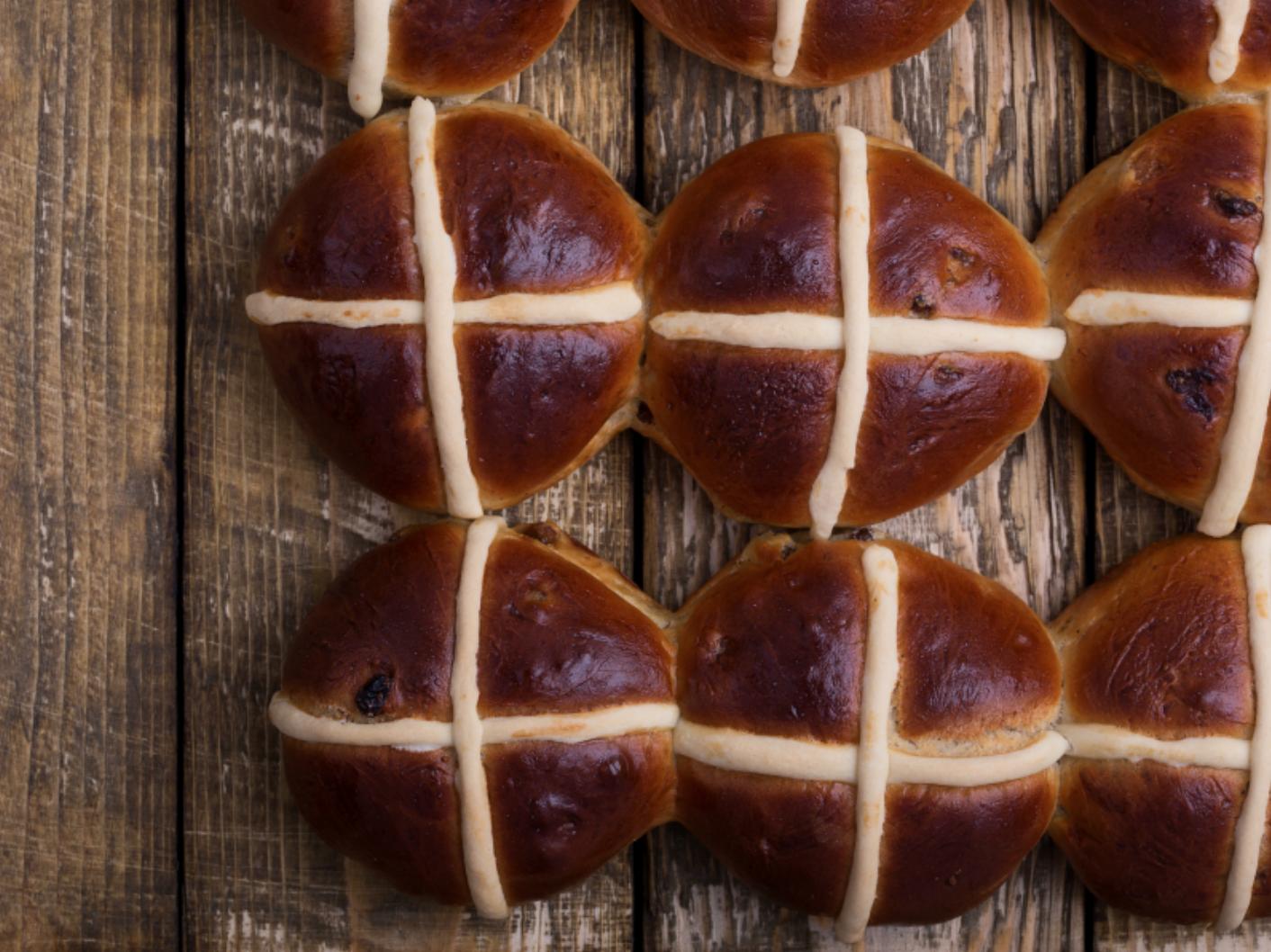 hot cross buns sitting on cutting board