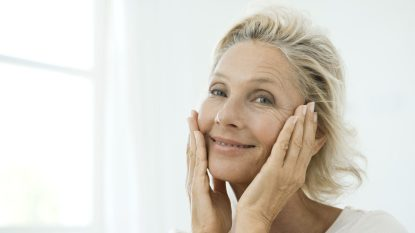 Mature woman touching cheeks, smiling, portrait