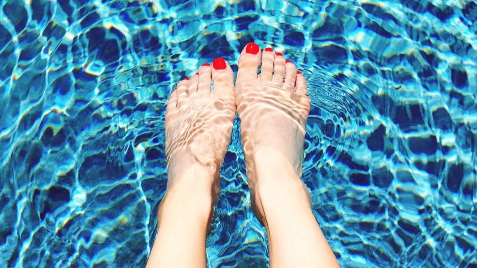woman's pedicured feet in swimming pool