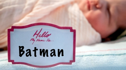 """Newborn in hospital bed with name tag reading """"Hello, my name is... Batman"""""""