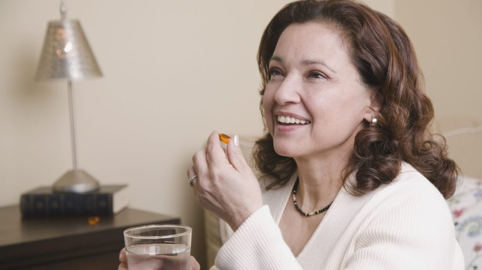 Mixed race woman taking vitamin