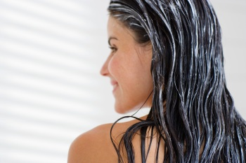 woman smiling with product in her hair in the shower