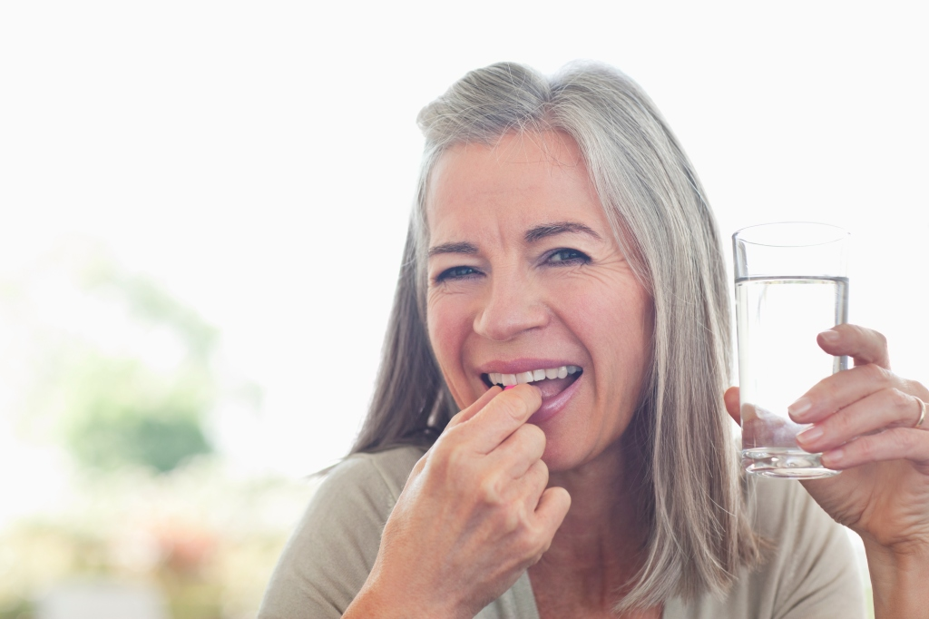 older woman smiles as she prepares to take a vitamin while holding a glass of water