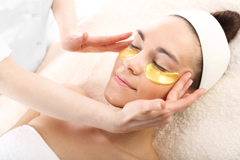 woman relaxing in a spa setting with gold under eye masks