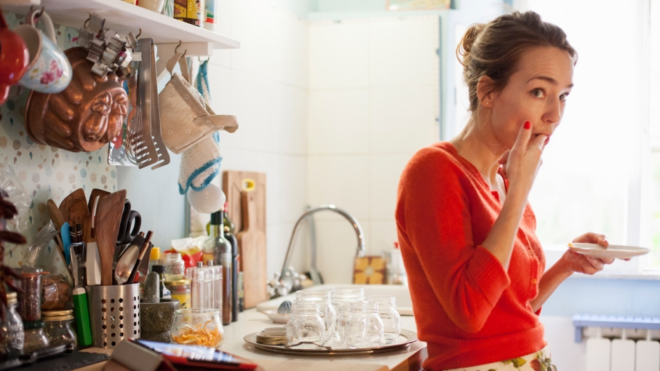 Woman eating in the kitchen