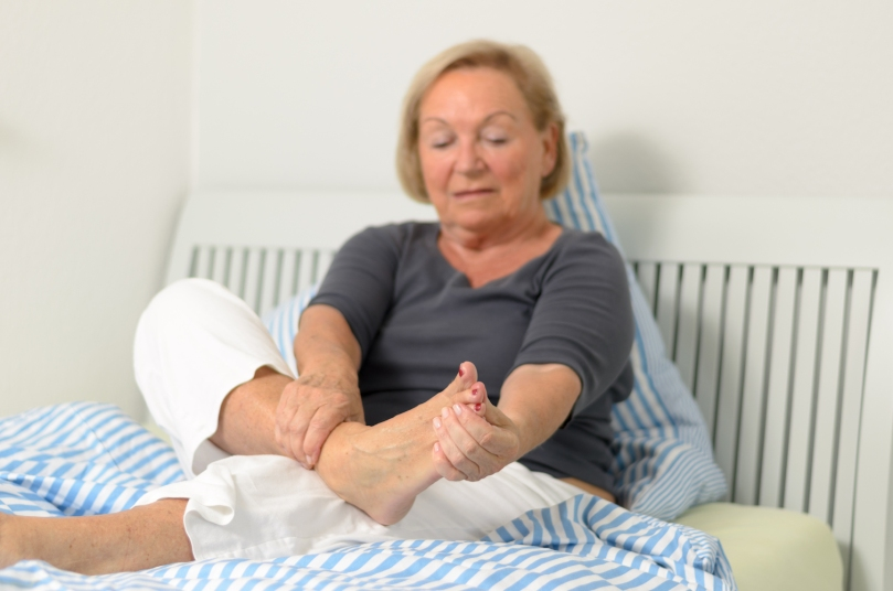 older woman holding painful foot