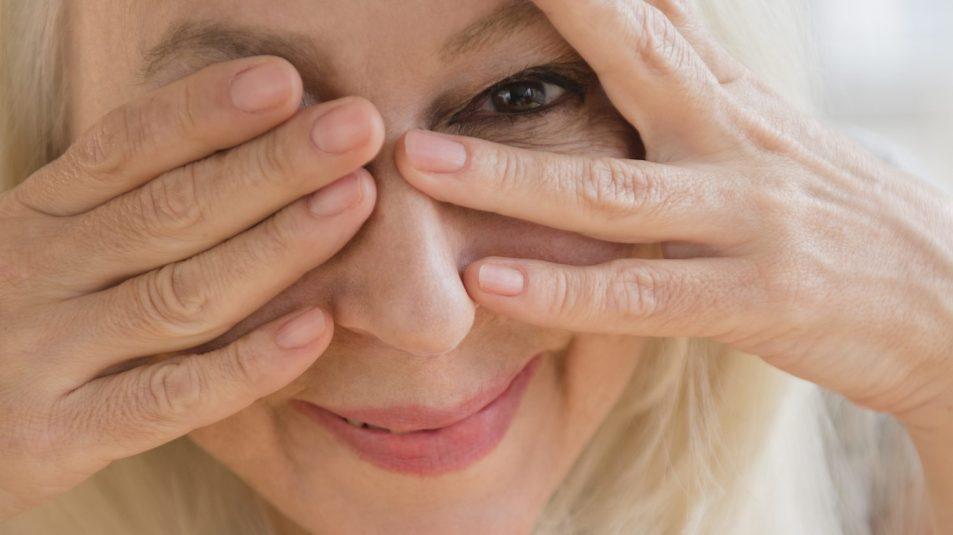 Caucasian woman peeking from behind eyes