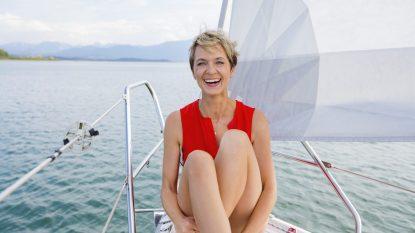 Mature woman sailing on Chiemsee lake, portrait, Bavaria, Germany