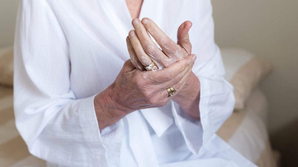 Elderly woman using handcream
