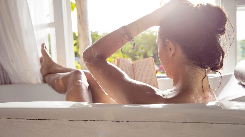 Woman relaxing in bathtub reading book