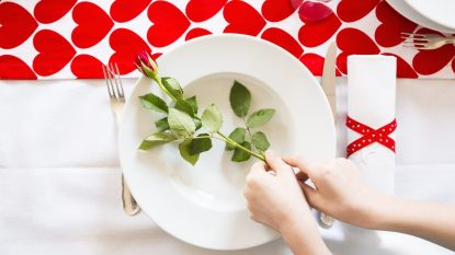 Hands putting rose on dish at laid table