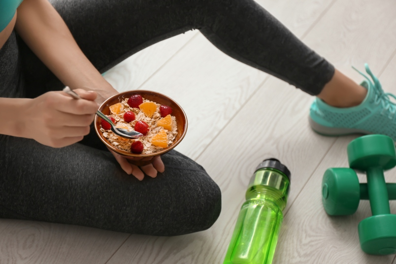 woman eating tasty oatmeal after training indoors