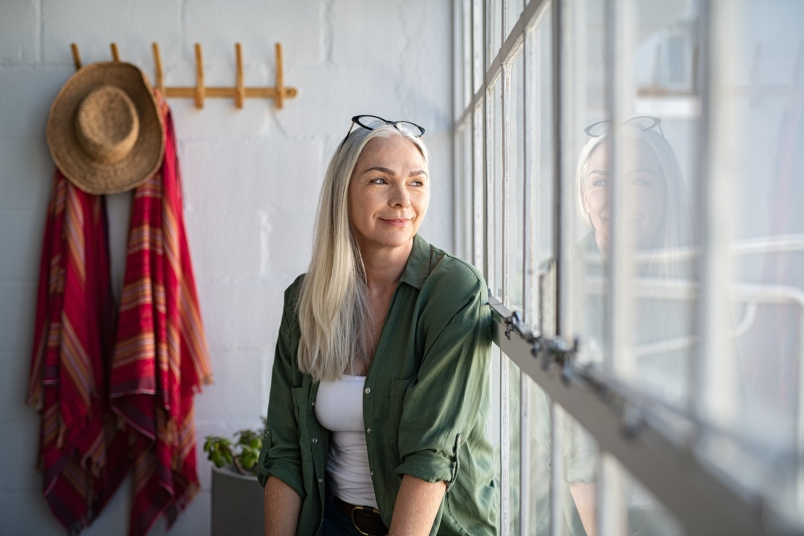 Happy mature woman looking out the window