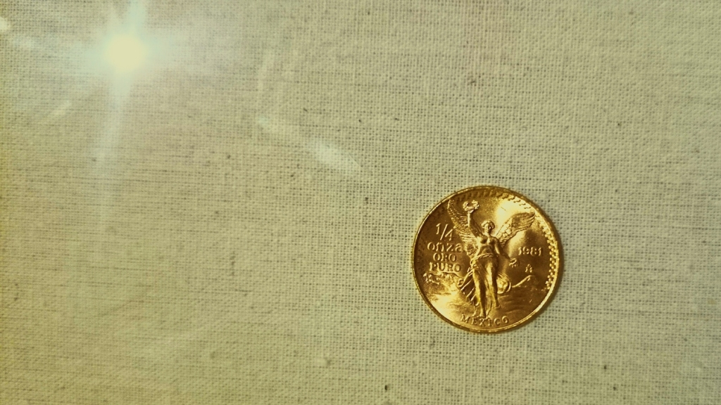 Directly Above Shot Of Mexican Coin On Fabric