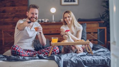 Couple having a breakfast in bed and watching TV