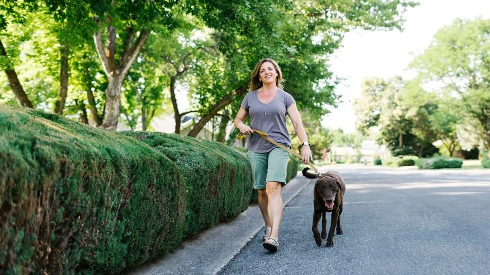 woman walking dog wearing shorts