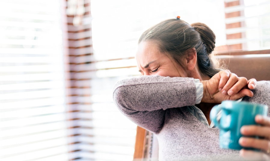 Woman coughs into elbow working form home