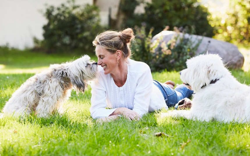 portrait of a mature content woman getting kisses from her dog in her garden