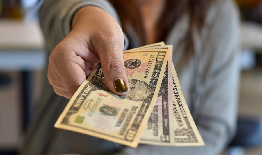 woman holding out cash