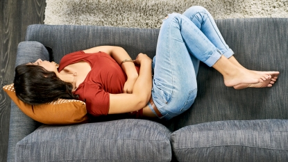 Woman clutching stomach curled up on couch