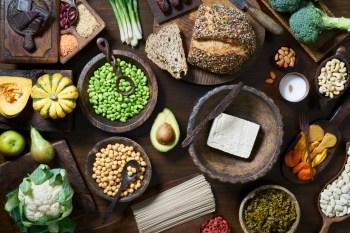 Overhead shot of healthy vegan food including fruit vegetables tofu and beans