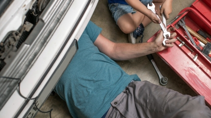 Dad and son working under a car