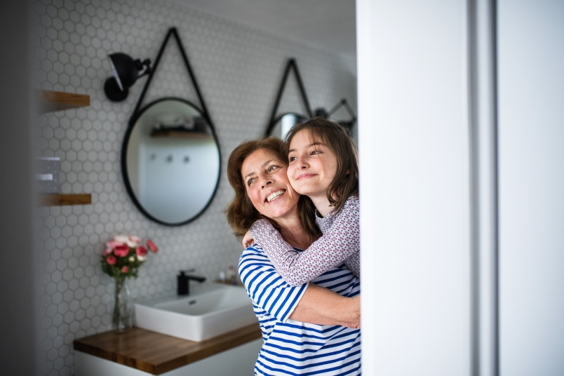 A small girl with grandma in bathroom.