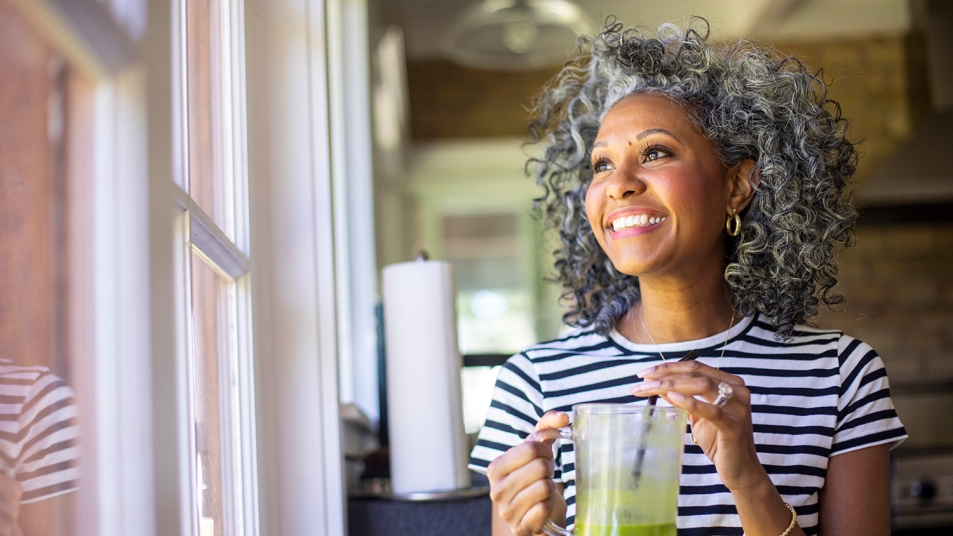 Black woman drinking a smoothie and smiling