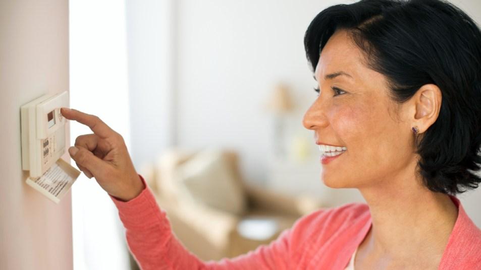 Woman adjusting air conditioning setting