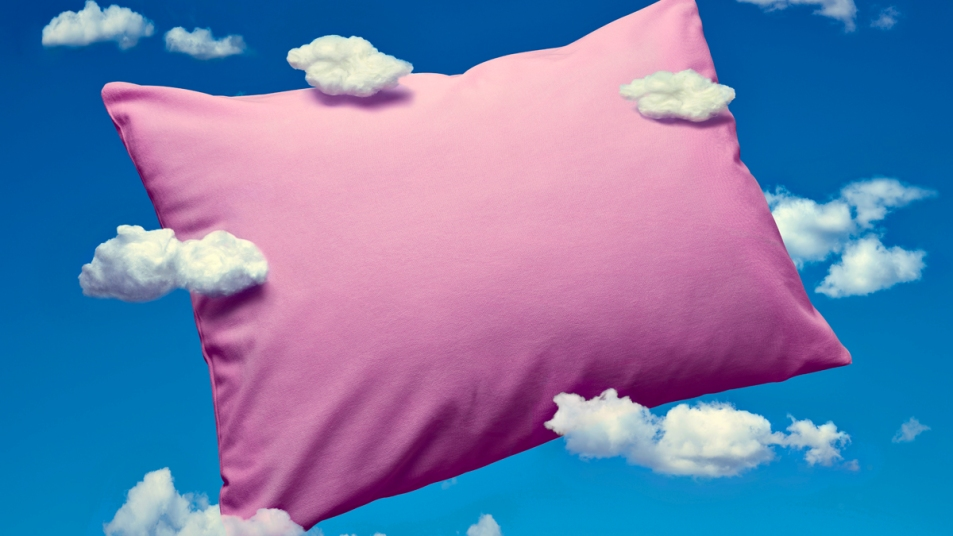 Pink pillow with a blue background and clouds representing dreams