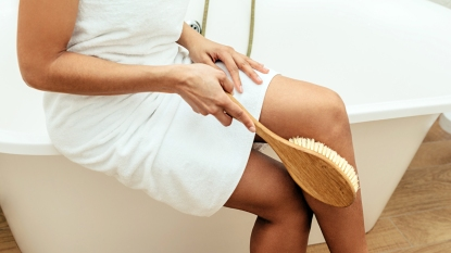 Lower half of a woman using a dry brush on skin