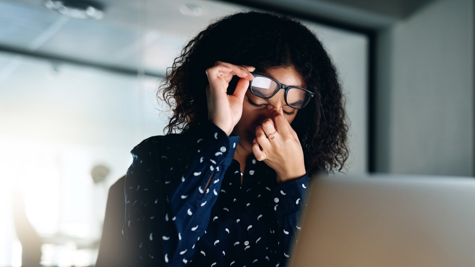 woman sitting in front of computer rubbing her eyes