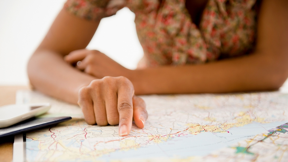 Woman's hand pointing to town on a map