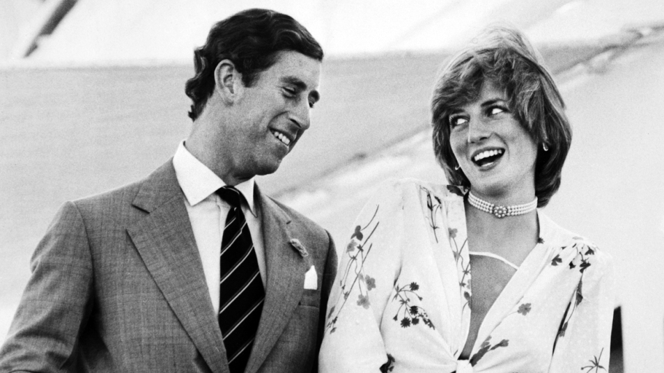Black and white photo of Princess Diana in a white and floral dress laughing with Prince Charles in a suit at an event before their wedding