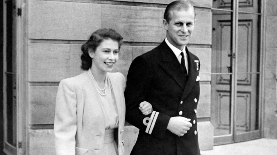Young Queen Elizabeth and Prince Philip walking arm in arm