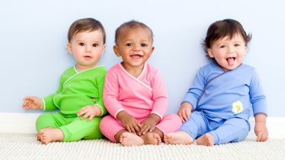 Babies in green, pink, and blue onesies