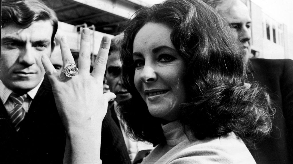 Elizabeth Taylor showing off her massive diamond ring from Richard Burton