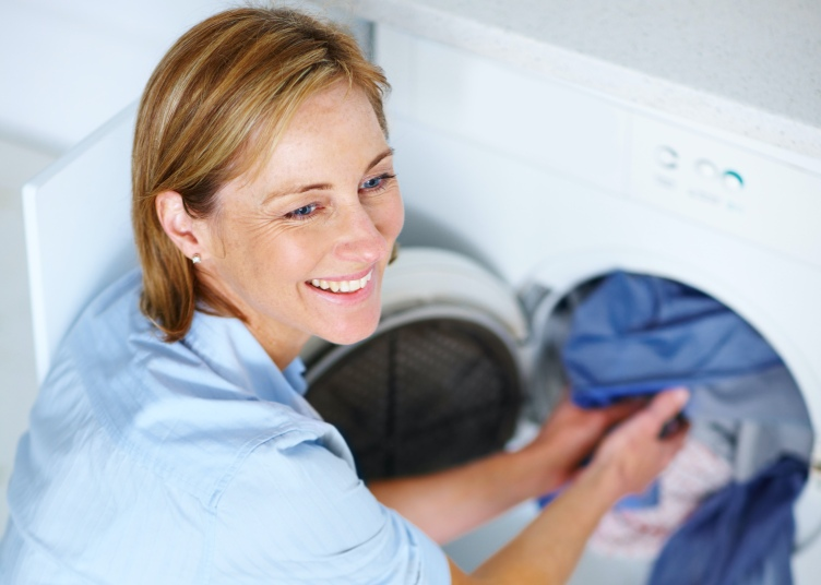 Smiling mature woman doing laundry at home