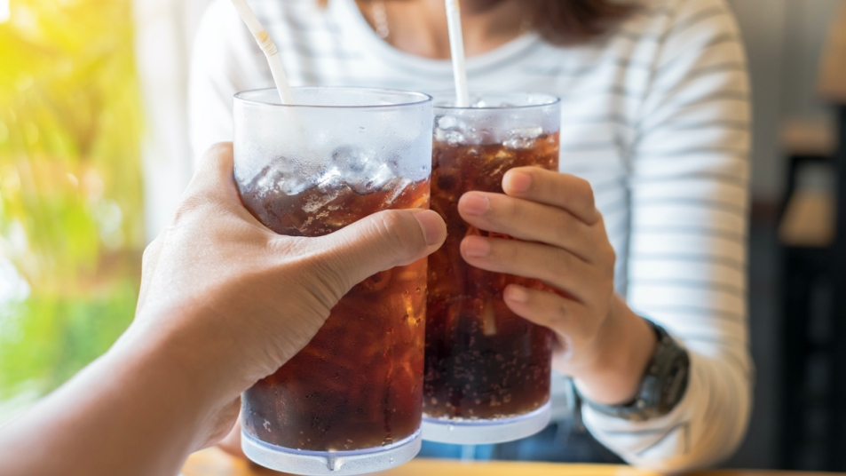 People's hands holding glasses of dark soda