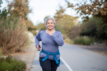 A mature woman jogging on a trail