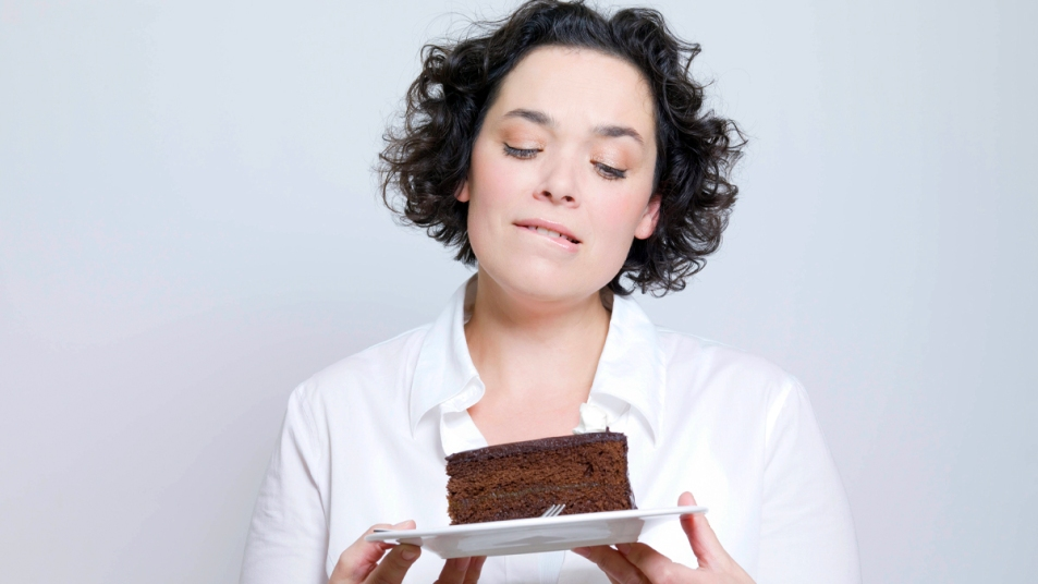 Woman looking at plate of chocolate cake