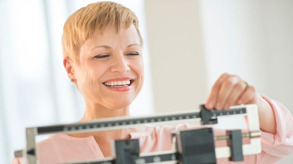 woman on scale losing weight smiling