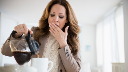 Woman yawning and pouring a cup of coffee