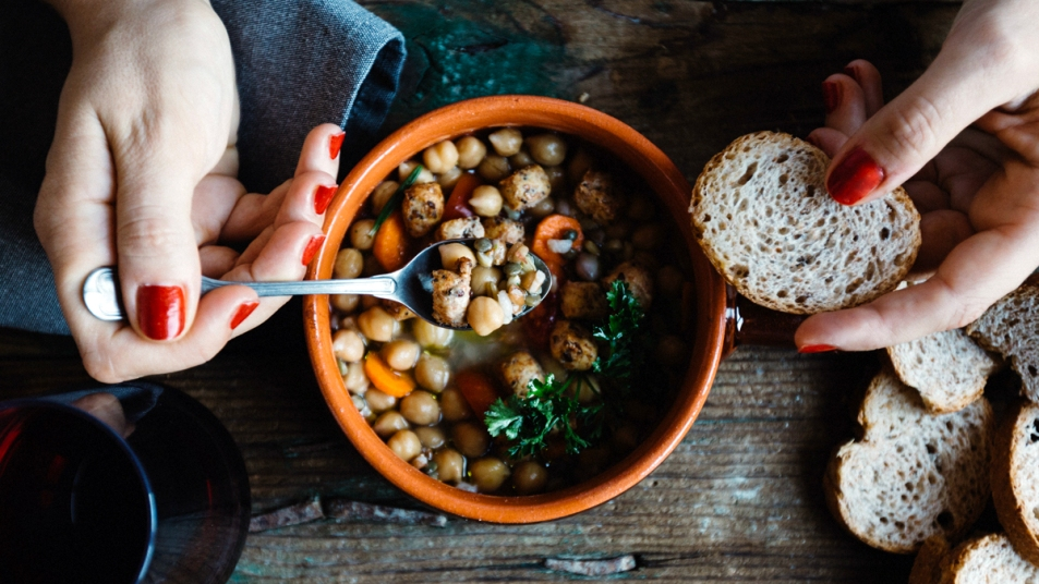 Woman's hands with bowl of bean soup