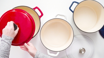 Hands removing lid from red dutch oven next to white and blue dutch ovens