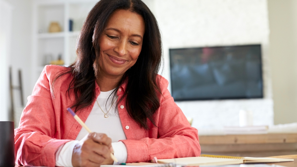 Woman smiling and writing on pad of paper