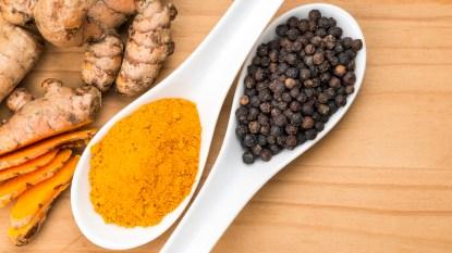 Spoonfuls of turmeric and black pepper corns