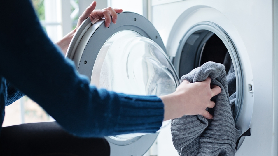 Woman putting in laundry into a washing machine